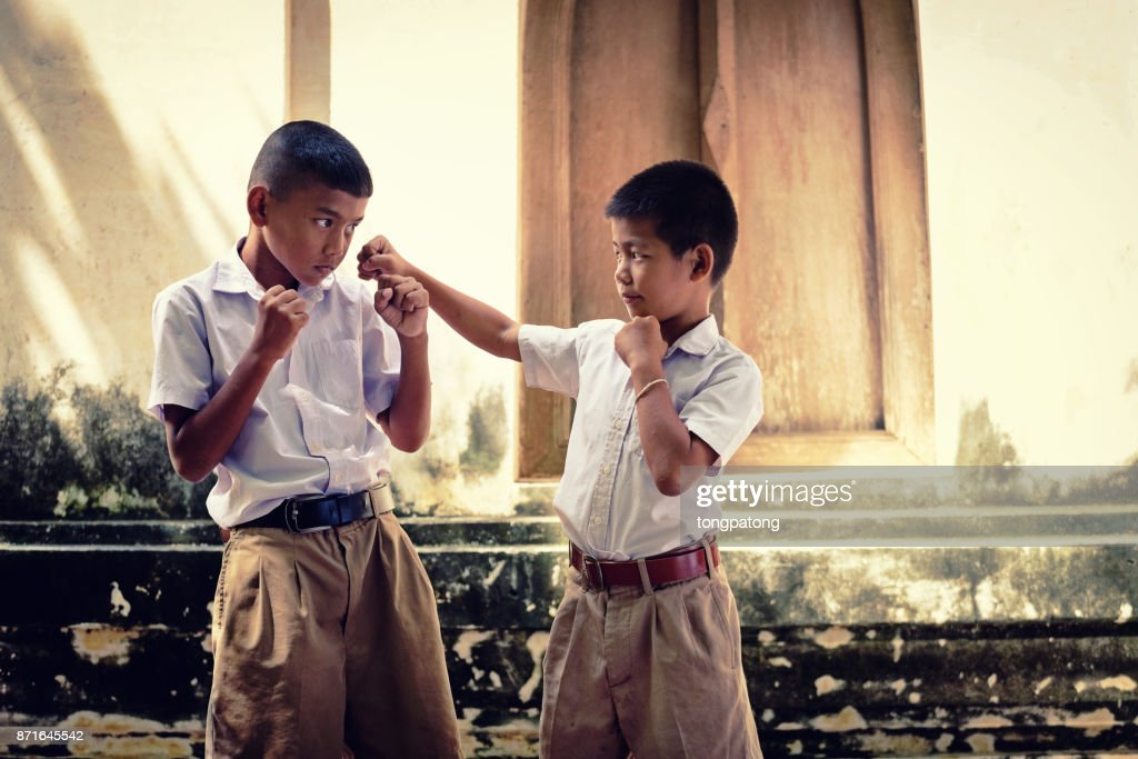 Two asian boys wearing school uniforms are playing boxing, old wall temple  background Local Thailand