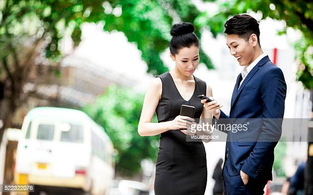 Two Asian Business Partners Exchanging Data On The Street