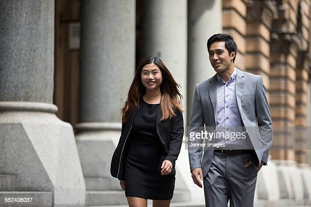 Two Asian Business people walking outdoors.