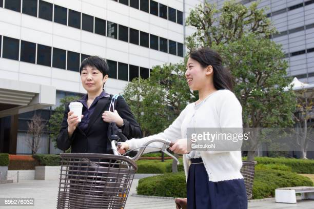 Two asian businesswomen have conversation on the way to office