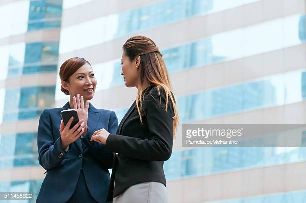 Two Asian Businesswomen in Discussion with Smartphone Outside Office Building