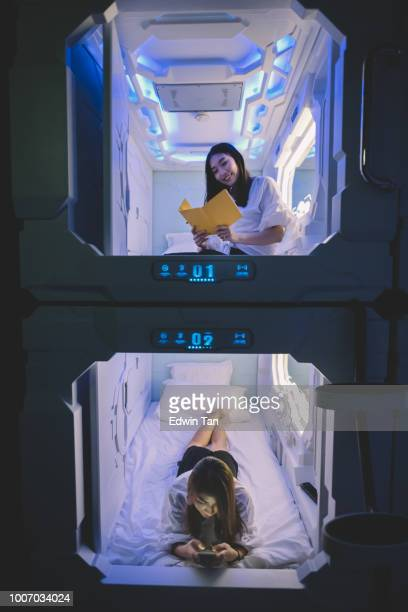 two asian chinese female tourist check in capsule hotel room and one surfing internet on her bed with her mobile phone while the other one  reading from her notebook