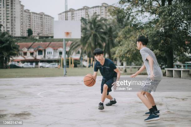 two asian chinese teenage boys playing and practicing basketball in the basketball court after school