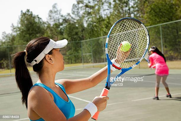 Two Asian descent women friends enjoy game of tennis. Court.