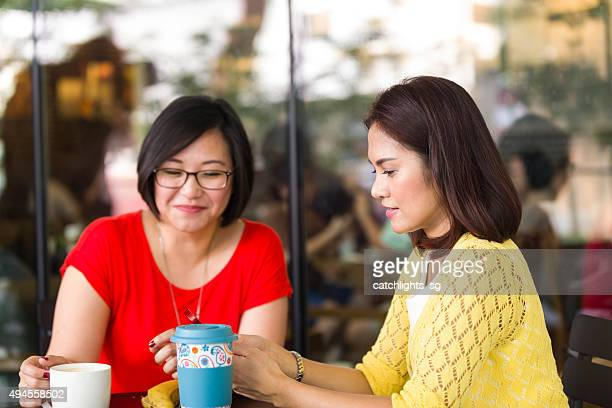 Two Asian Female Friends Hang Out at Outdoor Cafe