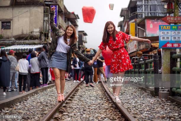 台湾の shefen で、手をつないで鉄道を楽しく歩く2人のアジアの女性観光客 - 台湾 ストックフォトと画像