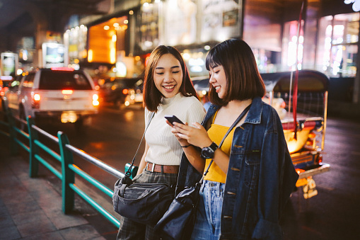 Two Asian girls in Bangkok, looking at their smartphones, chatting about social media - gettyimageskorea