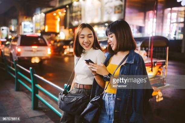 two asian girls in bangkok, looking at their smartphones, chatting about social media - south east asia stock pictures, royalty-free photos & images