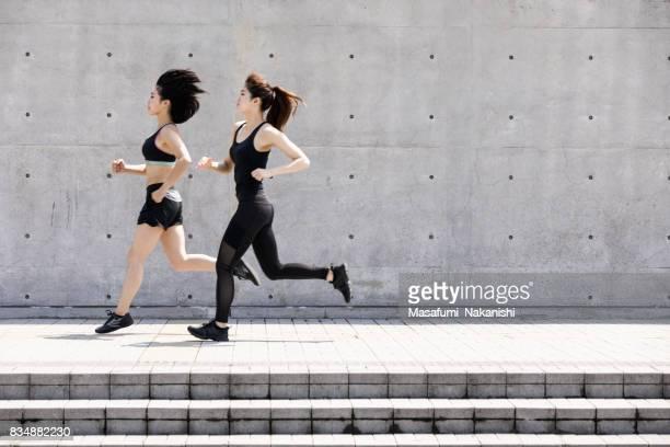 屋外を実行する 2 つのアジアの女性