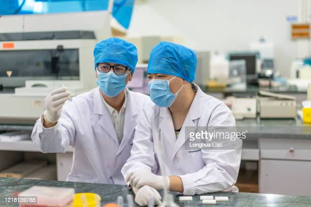 two asian male doctors work in the laboratory - china coronavirus stock pictures, royalty-free photos & images