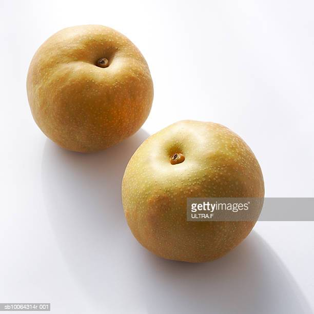 Two Asian pears (Pyrus pyrifolia var. culta) on white background