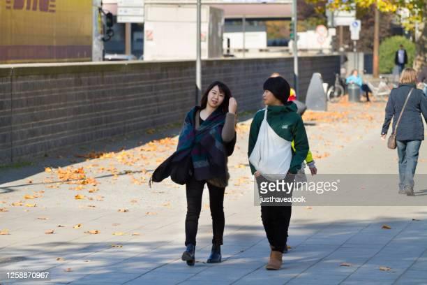 ケルンのライン川沿いを歩いている2人のアジア人観光客の女性 - ノルトラインヴェストファーレン州 ストックフォトと画像