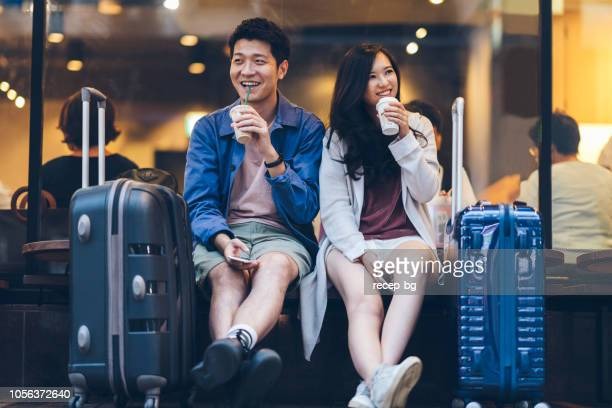 two asian tourists with suitcases spending happy time in cafe - turista foto e immagini stock
