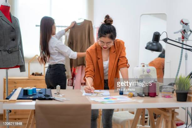 two asian woman at garment factory. they are happy and fashionable. they are standing behind sewing machines and design new dress. small business startup sme entrepreneur or freelance concept - design professional stock pictures, royalty-free photos & images