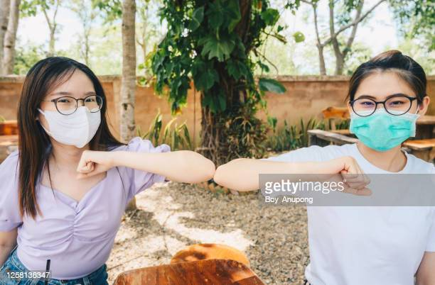 two asian woman doing elbows bump for greeting during coronavirus pandemic outbreak. - thailand stock pictures, royalty-free photos & images