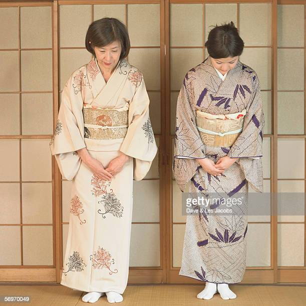 Two Asian women bowing