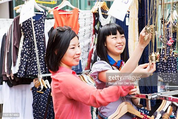 two asian women choosing jewellery at market
