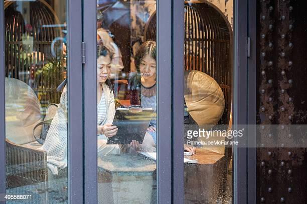 asiática dos mujeres tener un debate en un restaurante - voyeurismo fotografías e imágenes de stock