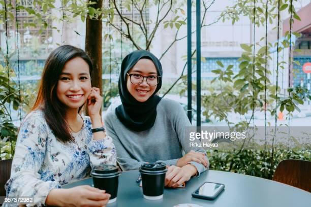 two asian women having break after meeting - rifka hayati stock pictures, royalty-free photos & images