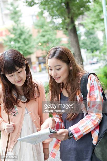 Two asian women having conversation over looking a