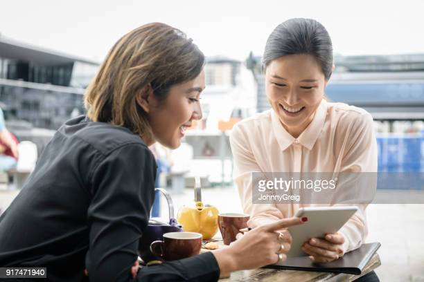 two asian women looking at digital tablet together - south east asian ethnicity stock pictures, royalty-free photos & images