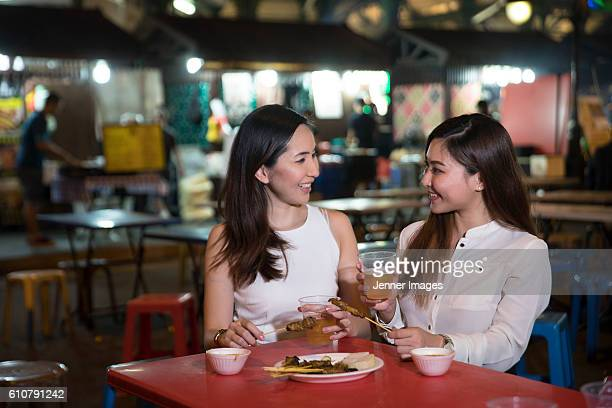 Two Asian women out for dinner at a street food market after work.