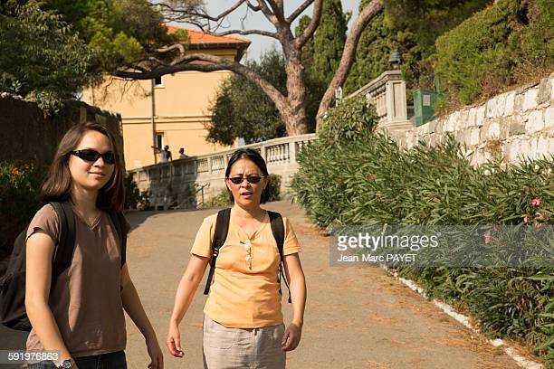 two asian women walking in the street - jean marc payet stock pictures, royalty-free photos & images