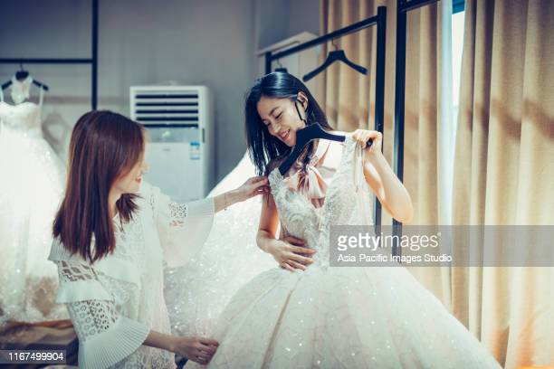 two asian young women shopping for wedding dress gowns in boutique discount store, many white garments hanging on rack hangers row. - abito da sposa foto e immagini stock