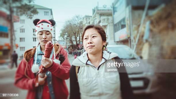 Two Asian young women walking on roadside.