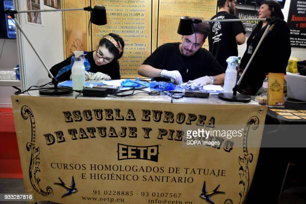 Two aspiring master trains with plates of silicone for practice with their style at the school of tattoo artists during the 2nd Spanish tattoo...