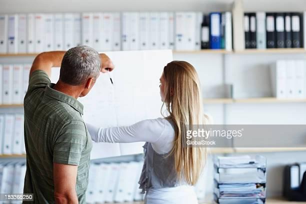 Zwei Mitarbeiter sehen und zeigt an Technische Zeichnung