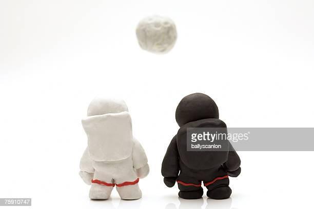 two astronauts made of clay facing moon, rear view - menschliche darstellung stock-fotos und bilder