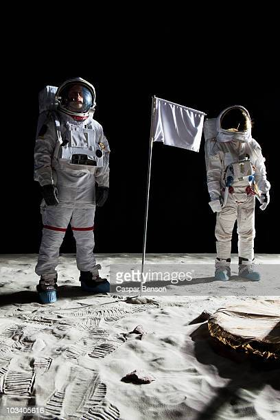 two astronauts on the moon, a blank white flag in between them - space helmet stock photos and pictures
