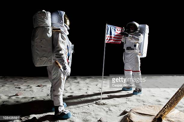 Two astronauts on the moon, an American flag in between them