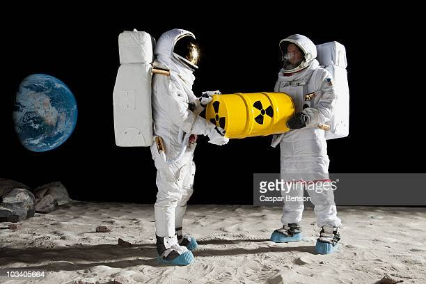 Two astronauts on the moon surface carrying a drum of toxic material
