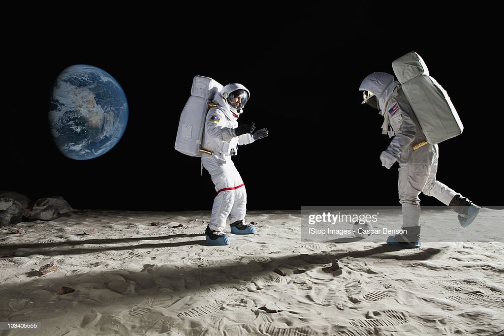 Two astronauts playing soccer on the moon : Stock Photo