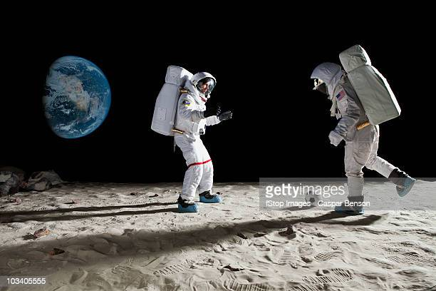 two astronauts playing soccer on the moon - astronauta fotografías e imágenes de stock