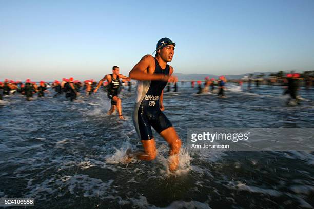 Two athletes approach the shore after completing the swim leg of the Los Angeles Triathlon while another group of athletes head out in to the water...
