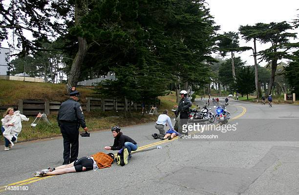 Two athletes are attended to by fans and police after a crash during the bike portion of the Escape from Alcatraz Triathlon on June 3 2007 in San...