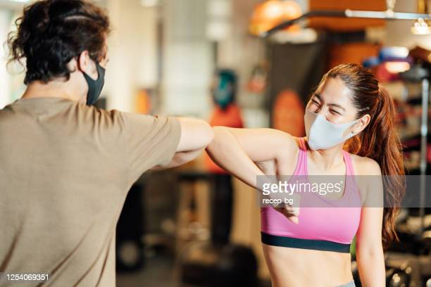 two athletes doing elbow bump to great each other in gym - elbow bump stock pictures, royalty-free photos & images