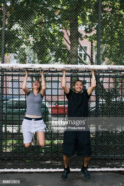 Two Athletes Doing Pull Ups On Goal Crossbar