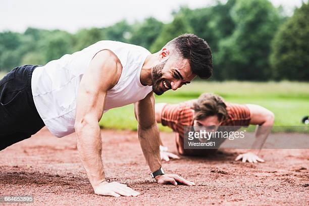 two athletes doing pushups on sports field - 腕立て伏せ ストックフォトと画像