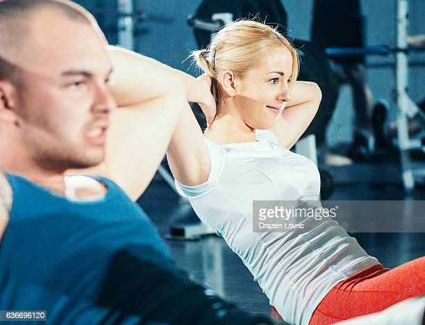 two athletes doing sit ups for abdominal muscles in gym - circuit training stock photos and pictures