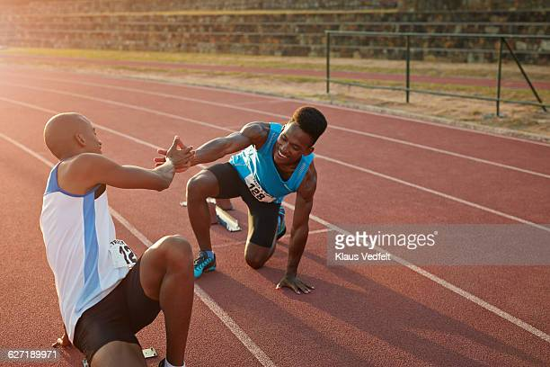 Two athletes giving high five, before sprint