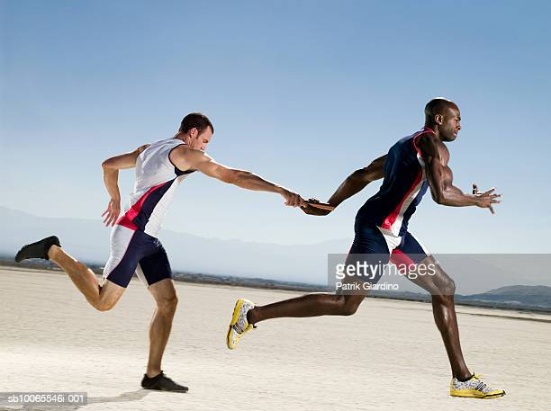 two athletes passing relay, side view - relay stock pictures, royalty-free photos & images