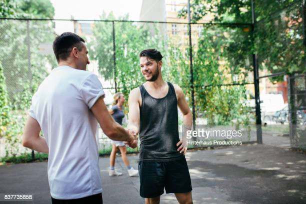 Two Athletes Shaking Hands Before Friendly Game Of Basketball Outdoors
