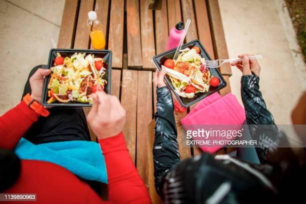 two athletes using plastic eating utensils to eat a healthy protein salad from a plastic take-out box while sitting together on a park bench - plastic plate stock photos and pictures