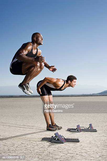 two athletes warming up at starting block, side view - el mirage dry lake stock photos and pictures