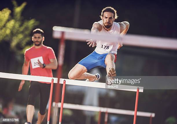 Two athletic men competing on a hurdle race.