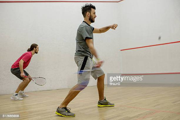 Two athletic men playing racketball on a court.